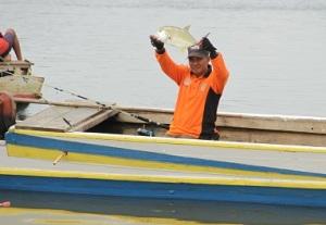 Seolah tak mau kalah, setelah 10 menit melempar pancing, Pak Tamsar berhasil menakhlukkan seekor ikan putih.